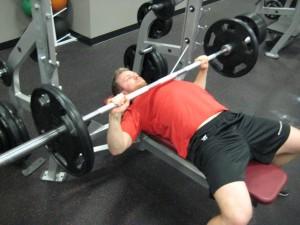 Špatná technika: Příliš lokty od těla - činka příliš vysoko.